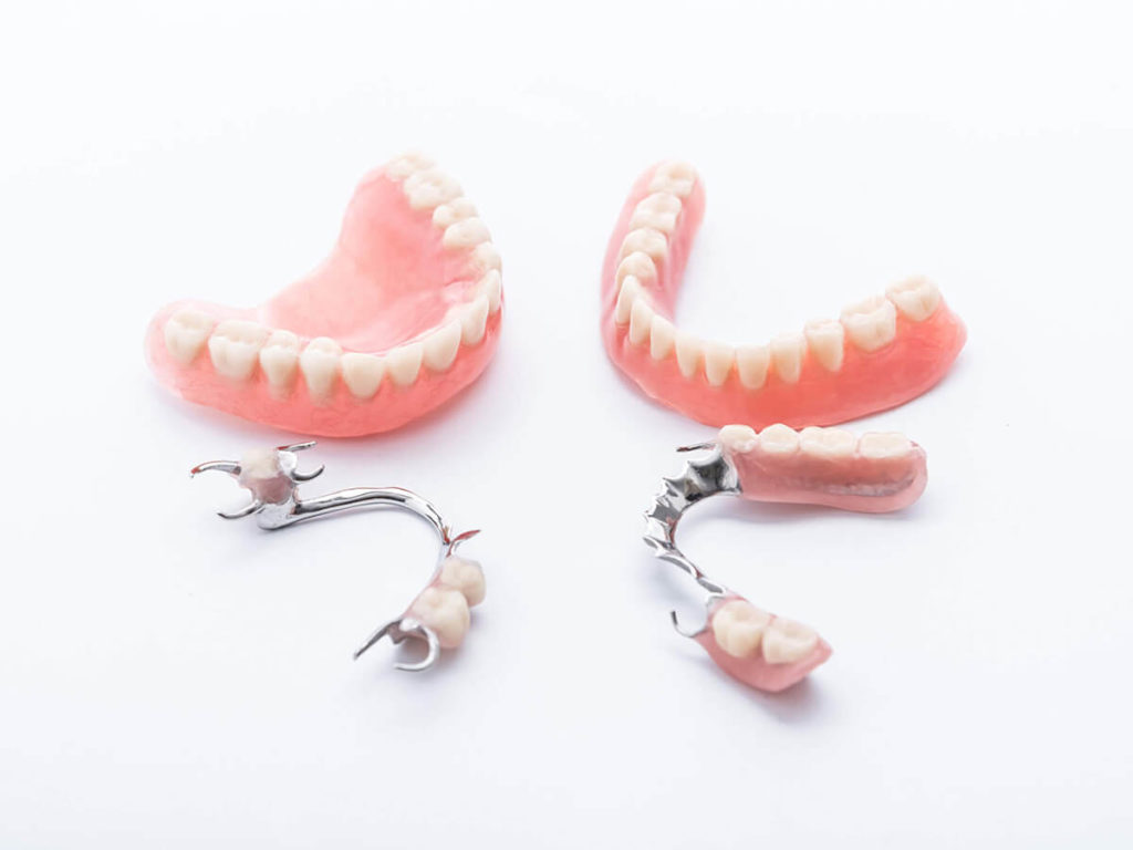 full and partial dentures on a white background