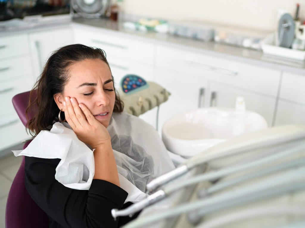 woman at a dentist office, holding her cheek in pain
