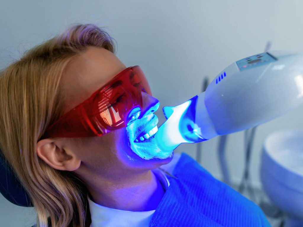 woman at the dentist getting a professional teeth whitening treatment, with a uv light shining on her teeth