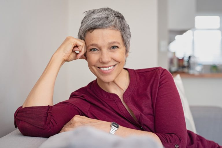 An older woman sitting on a couch and smiling