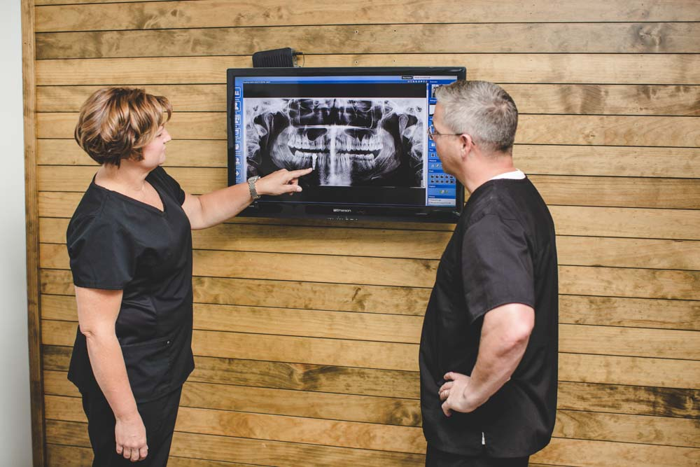Dentists discuss patient x-rays on a monitor