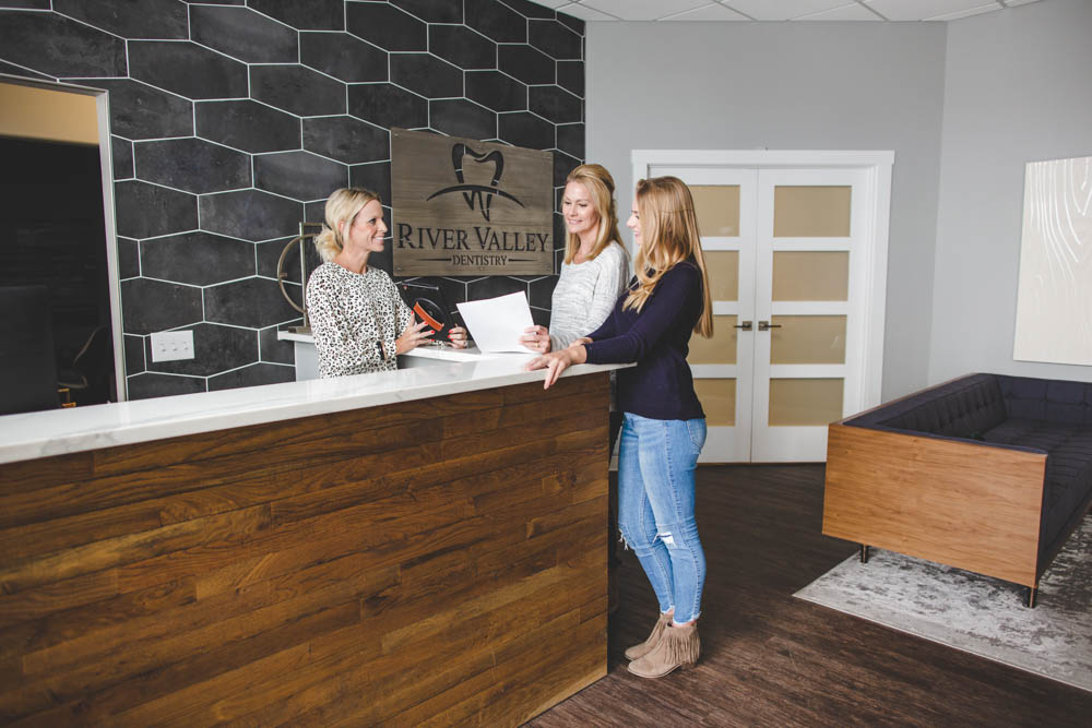 A receptionist helps patients at the front desk
