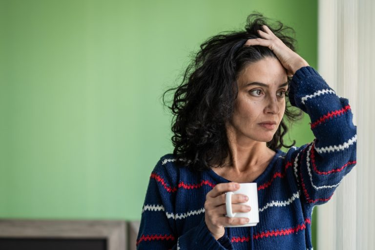 Image of a stressed woman holding a coffee mug