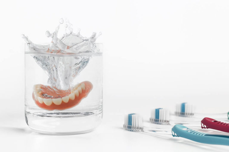 Dentures being dropped into a glass of water with a row of toothbrushes to the right of the glass