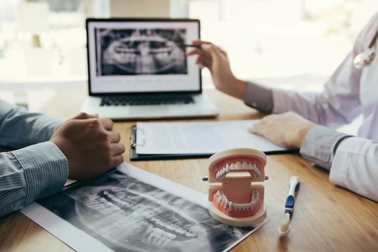 A dentist sits across a desk from a dental patient and discusses their smile design plan