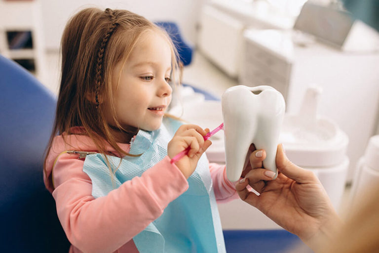 A young girl sits in a dental exam chair and brushes a model of a tooth that an out of view adult is holding