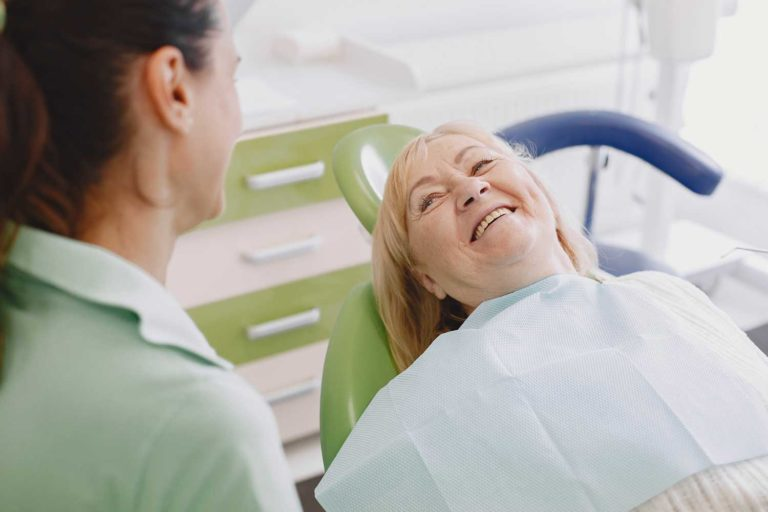 a senior aged woman sits at the dentist in the dental exam chair
